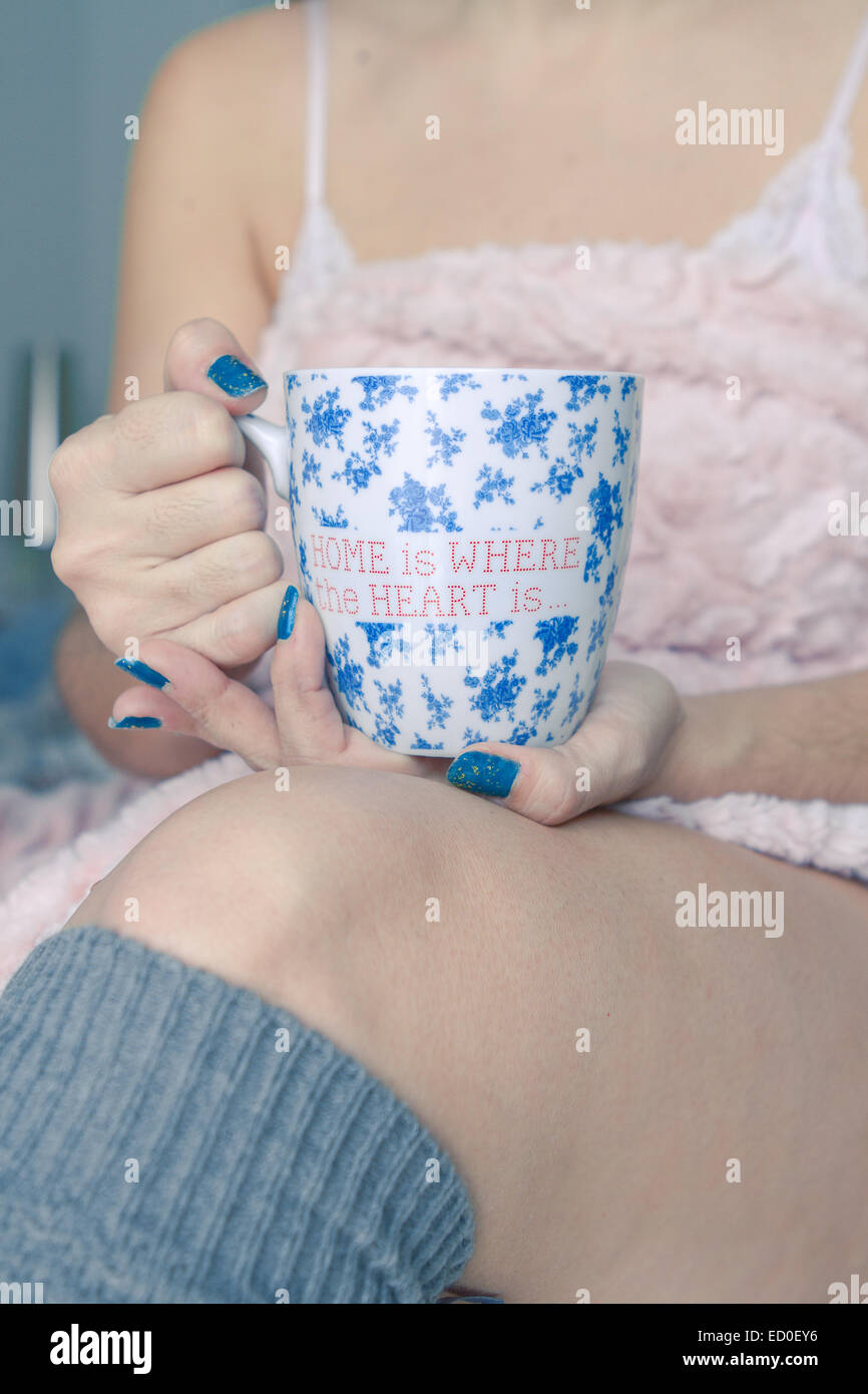Woman holding coffee mug - Stock Image
