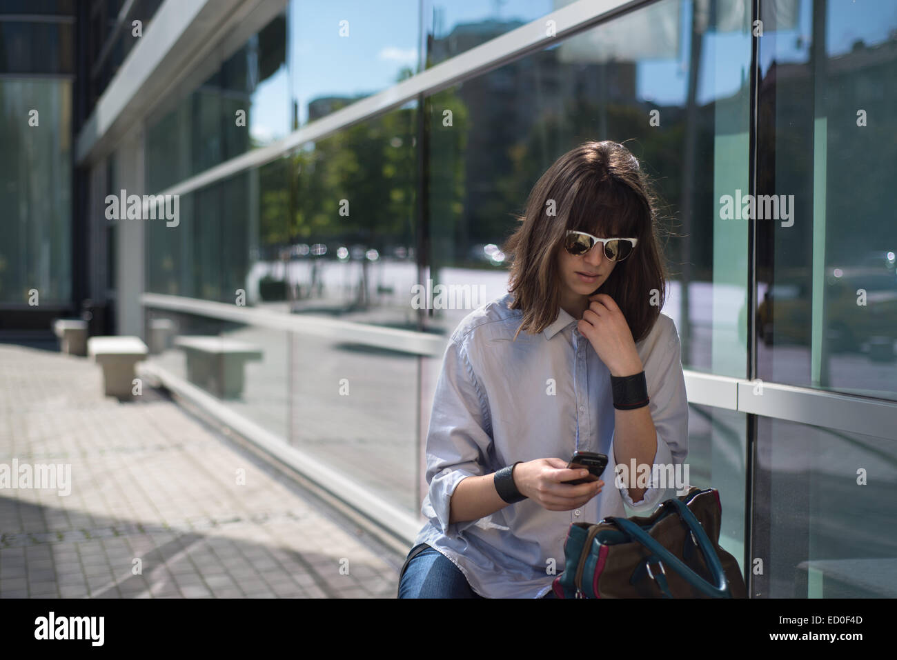 Woman sitting in street looking at mobile phone, Sofia, Bulgaria - Stock Image