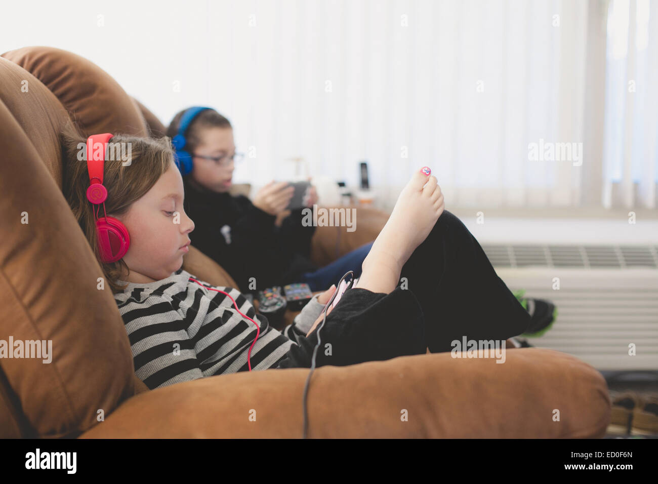 Brother and sisters listening to music - Stock Image