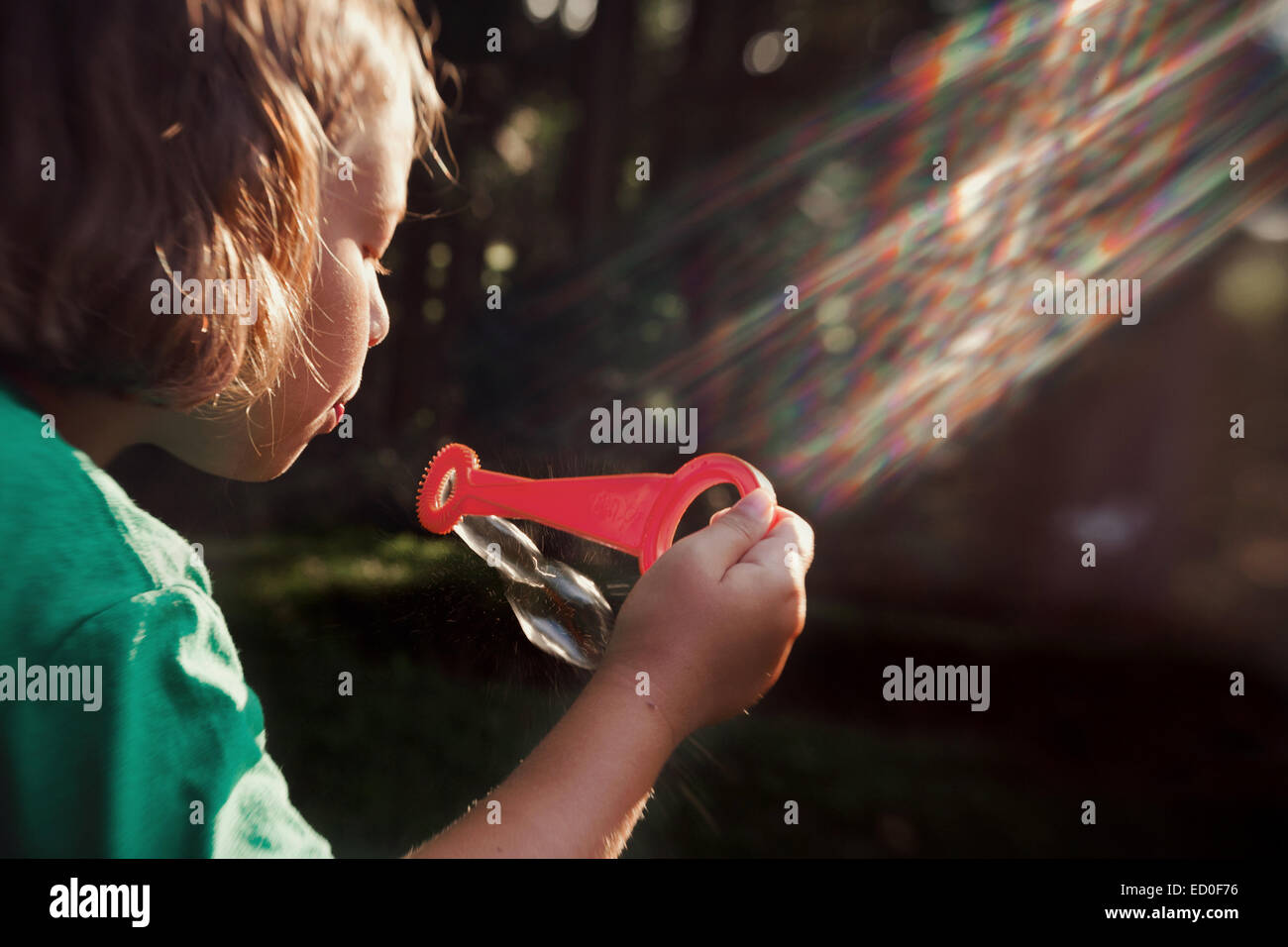 Girl (8-9) blowing bubbles - Stock Image