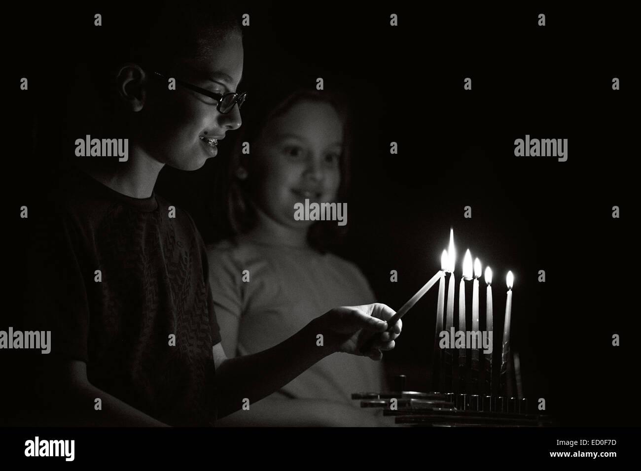Children (8-9) lighting Menorah - Stock Image