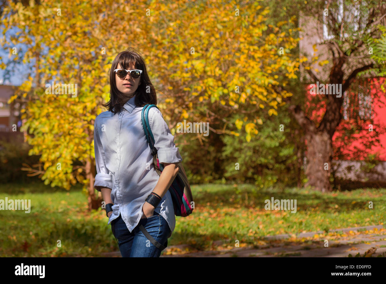 Portrait of young woman in autumn scenery - Stock Image