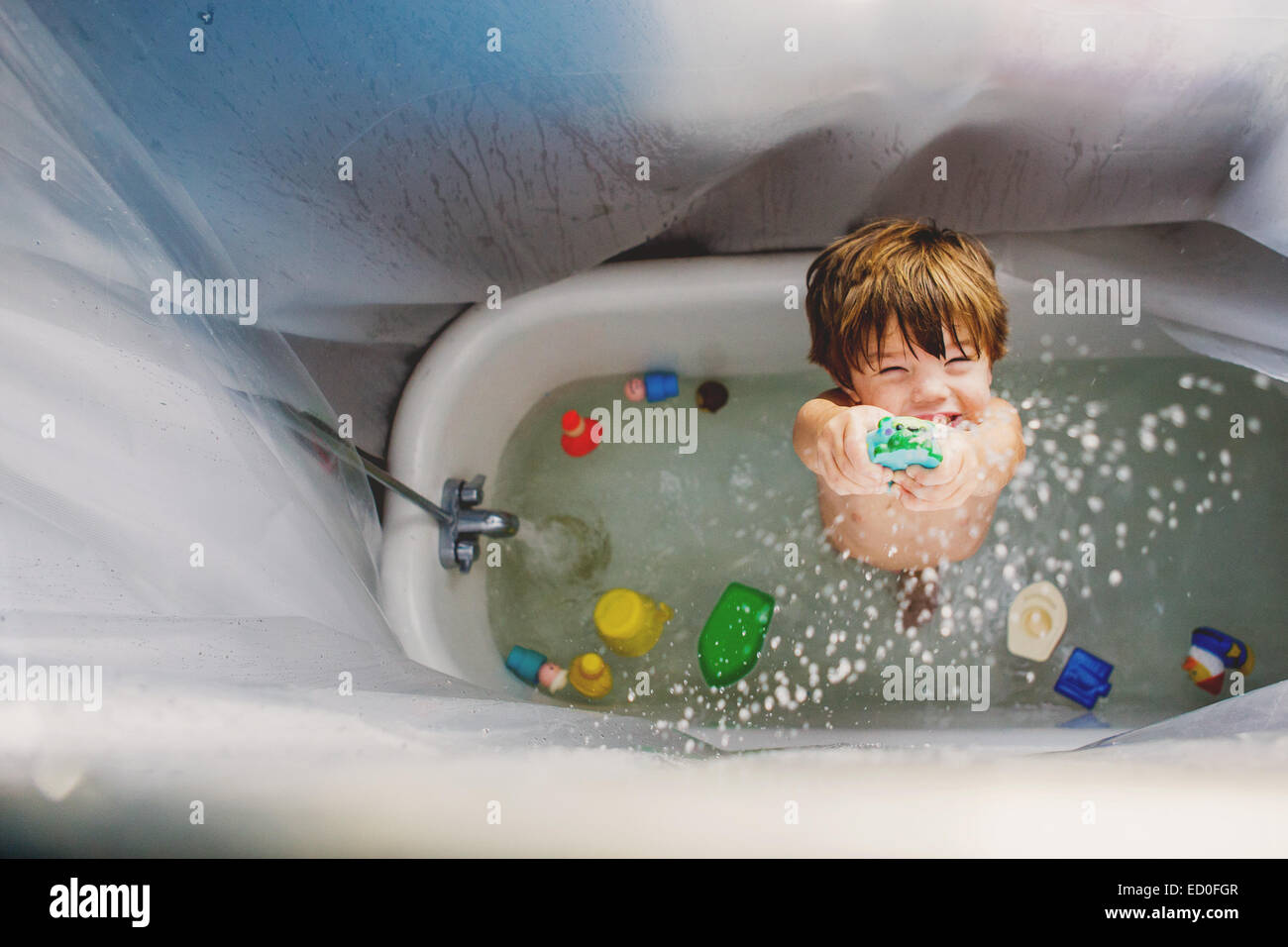 Overhead view of a boy standing in a bath playing with toys Stock Photo