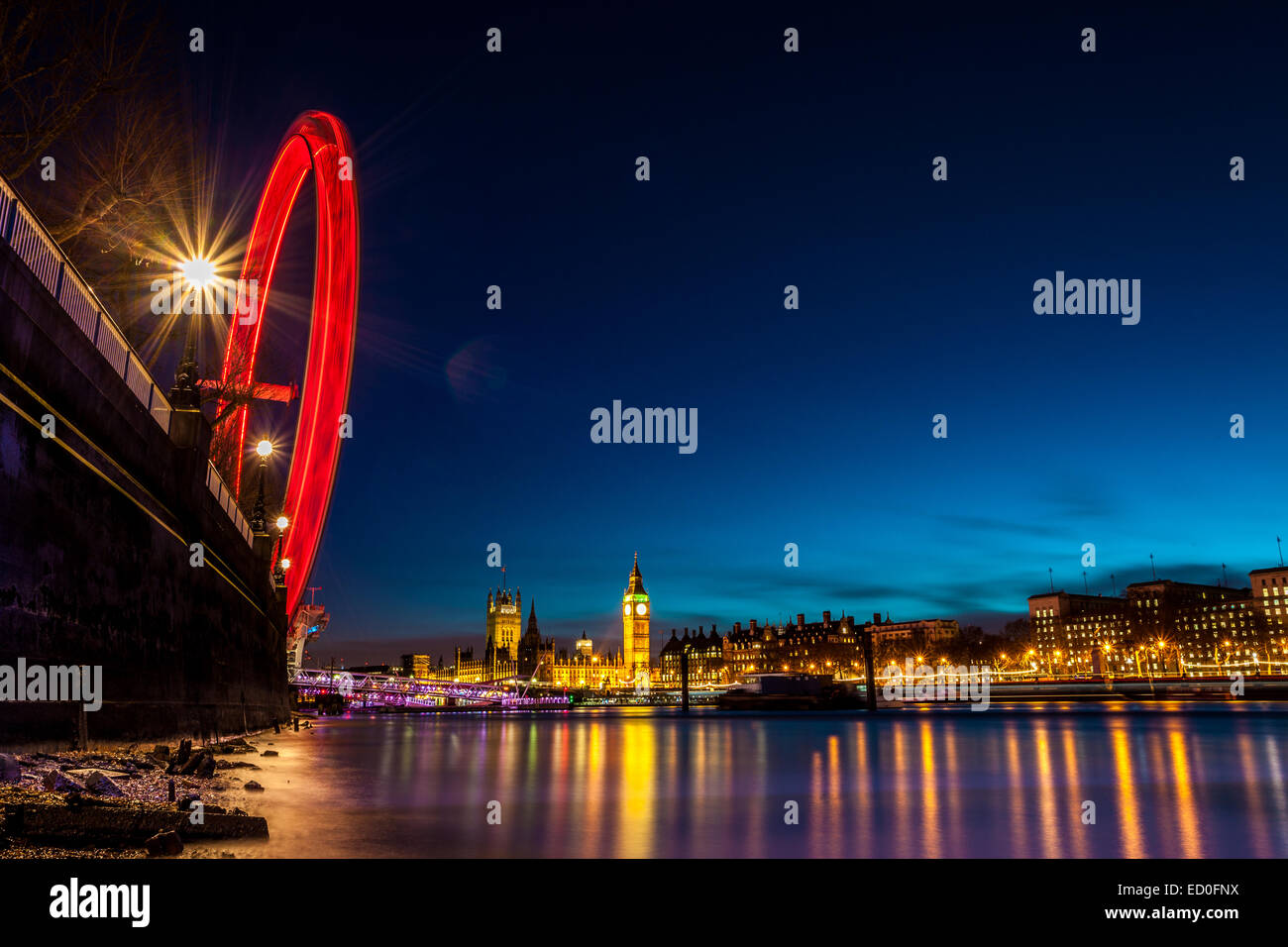 United Kingdom, England, London, London Eye, Westminster Bridge, London Eye in motion and illuminated cityscape - Stock Image