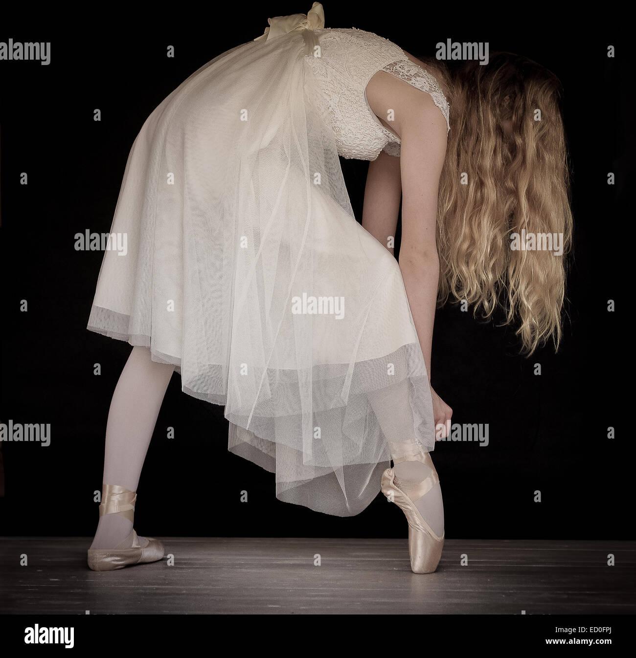 Ballet dancer adjusting ribbon on ballet shoes - Stock Image
