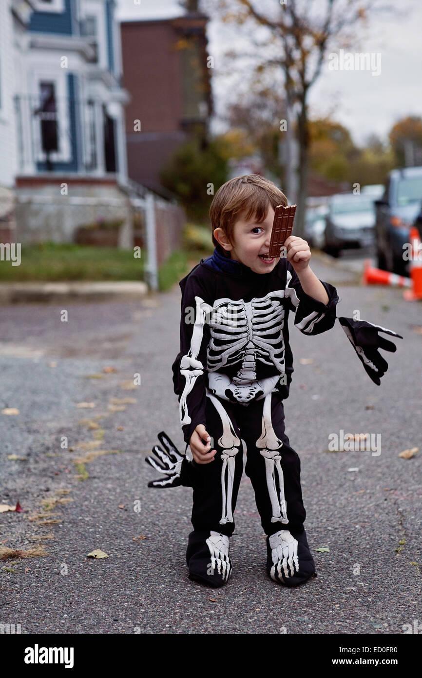 Smiling boy (2-3) in skeleton costume holding chocolate bar - Stock Image