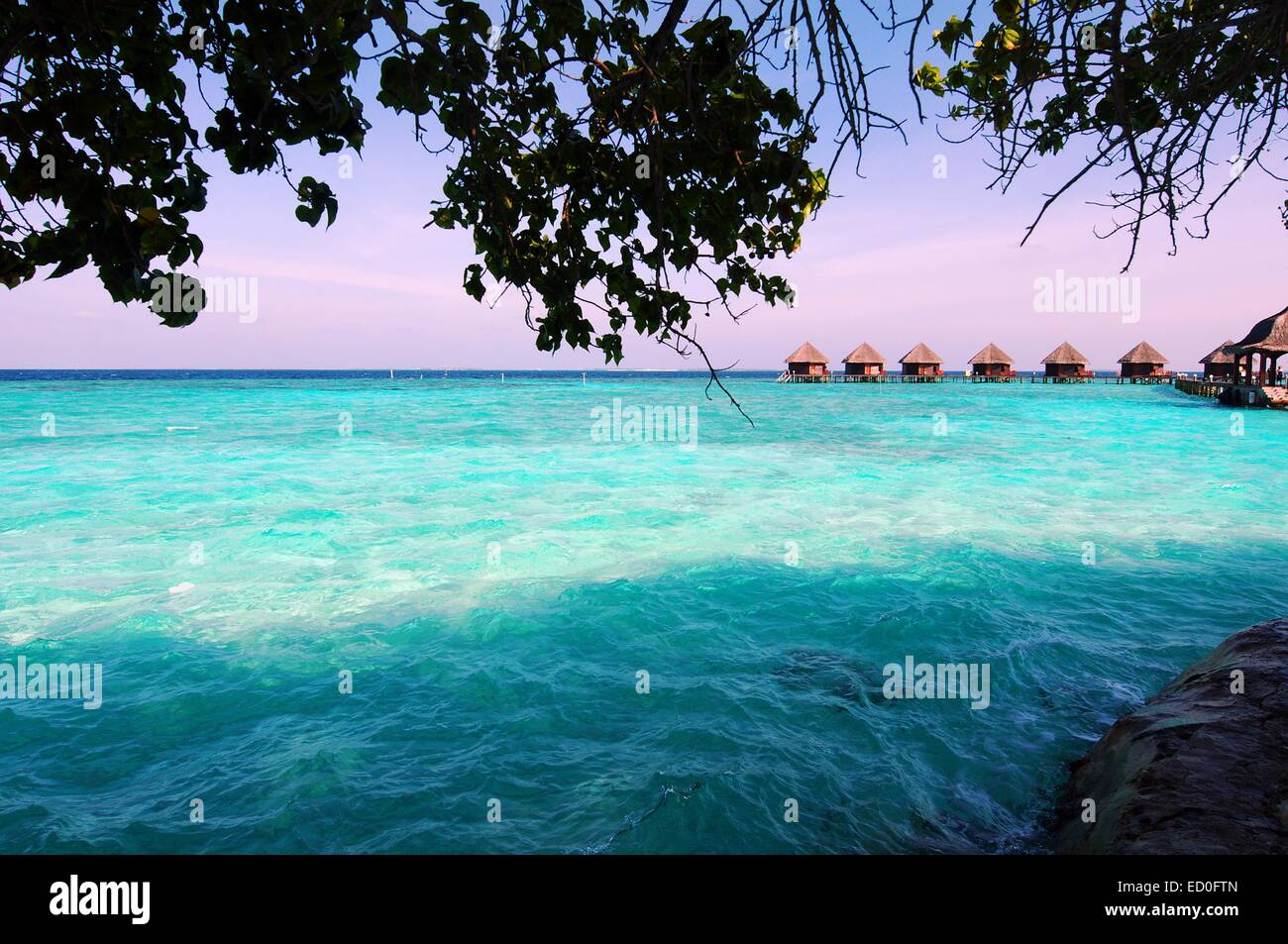 Maldives, Turquoise water and beach huts on horizon - Stock Image