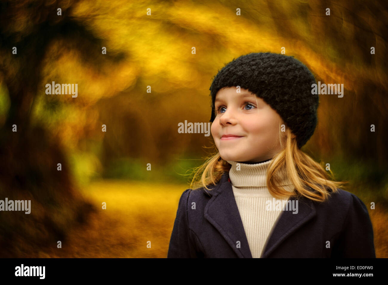 Girl (2-3) in woolly hat in autumn park - Stock Image