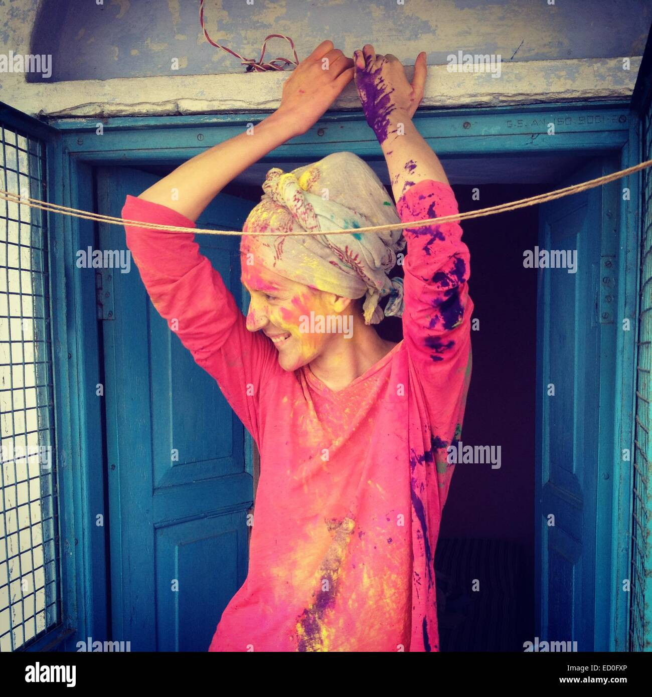 Young woman with headscarf and painted face leaning against blue door - Stock Image