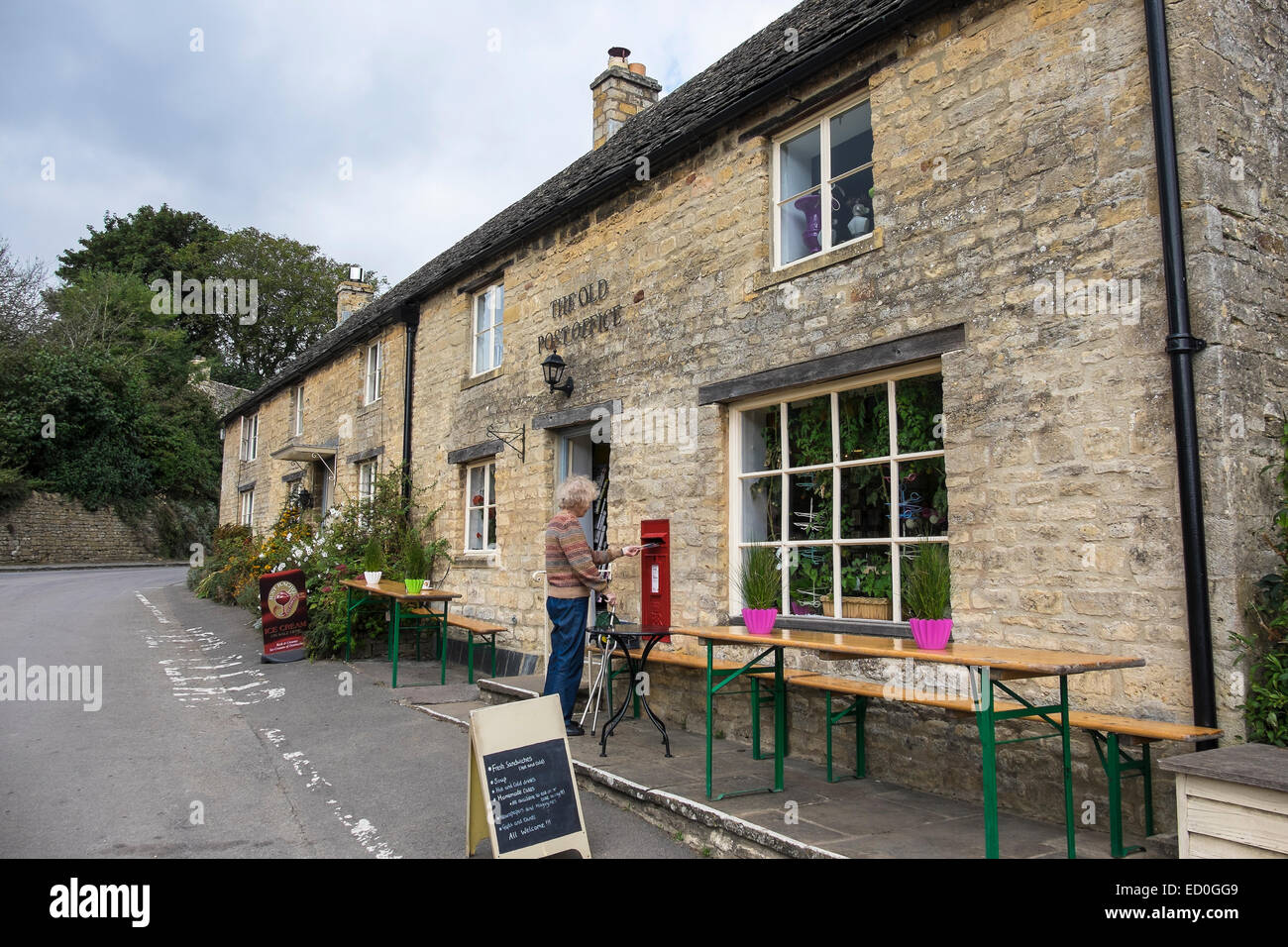 Lady posting The Old Post office and Cotswold stone cottages The Square Guiting Power The Cotswolds Gloucestershire - Stock Image