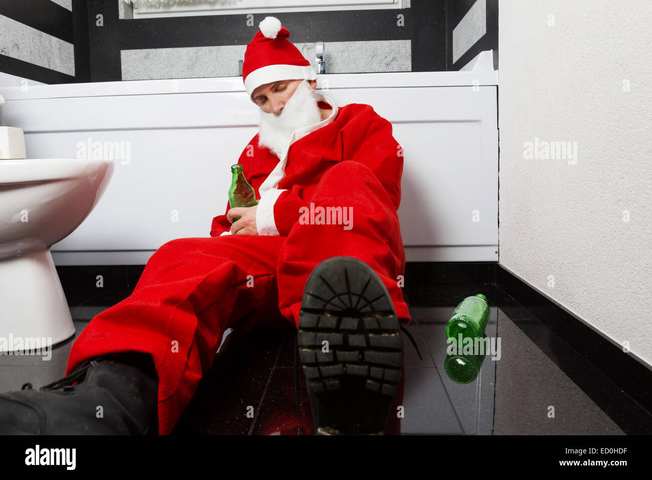 drunken santa claus sleeping at bathroom with beer bottle in hand after Sylvester party Stock Photo