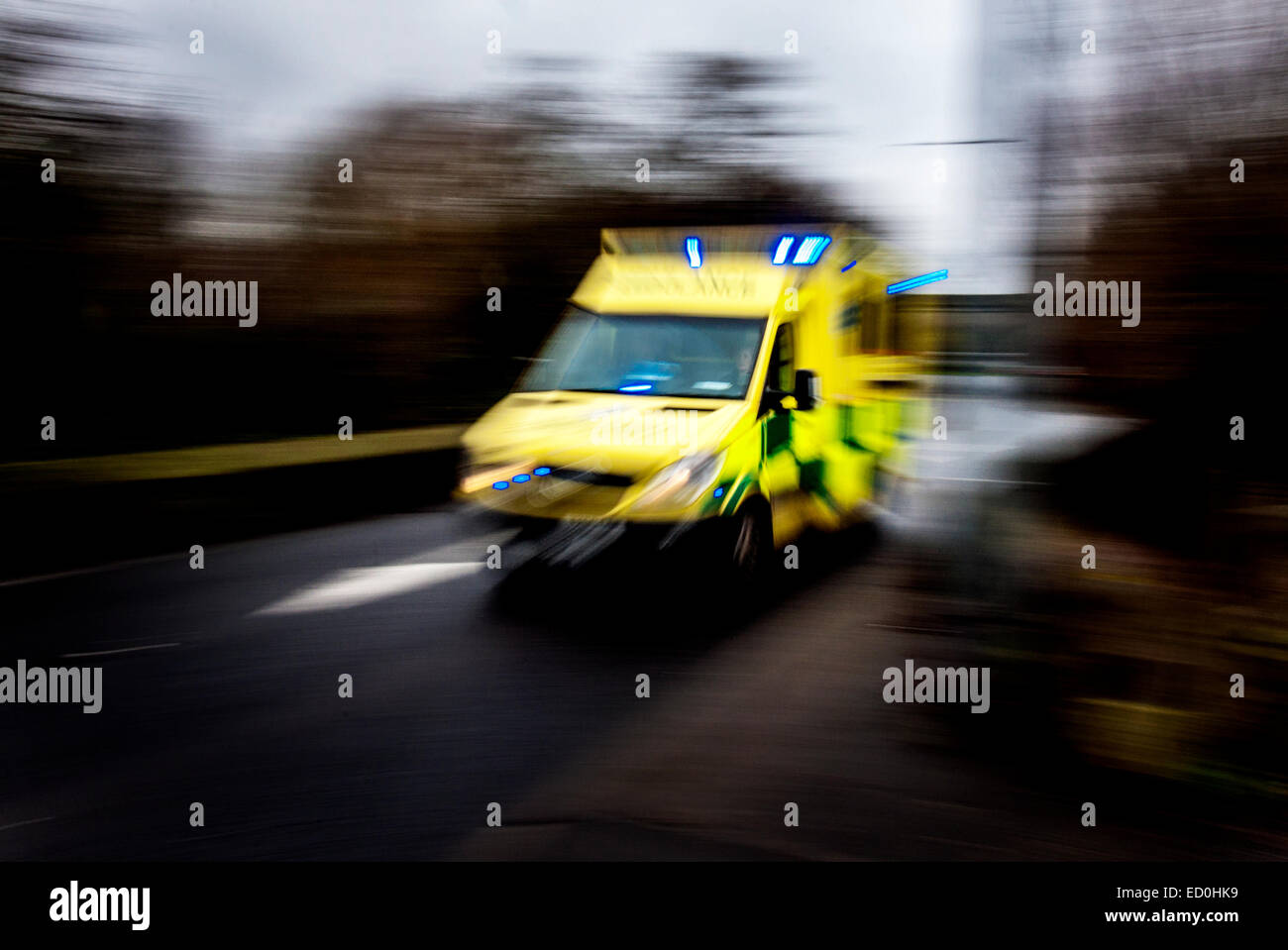 Fast moving ambulance responding to an emergency image showing speed blur. - Stock Image