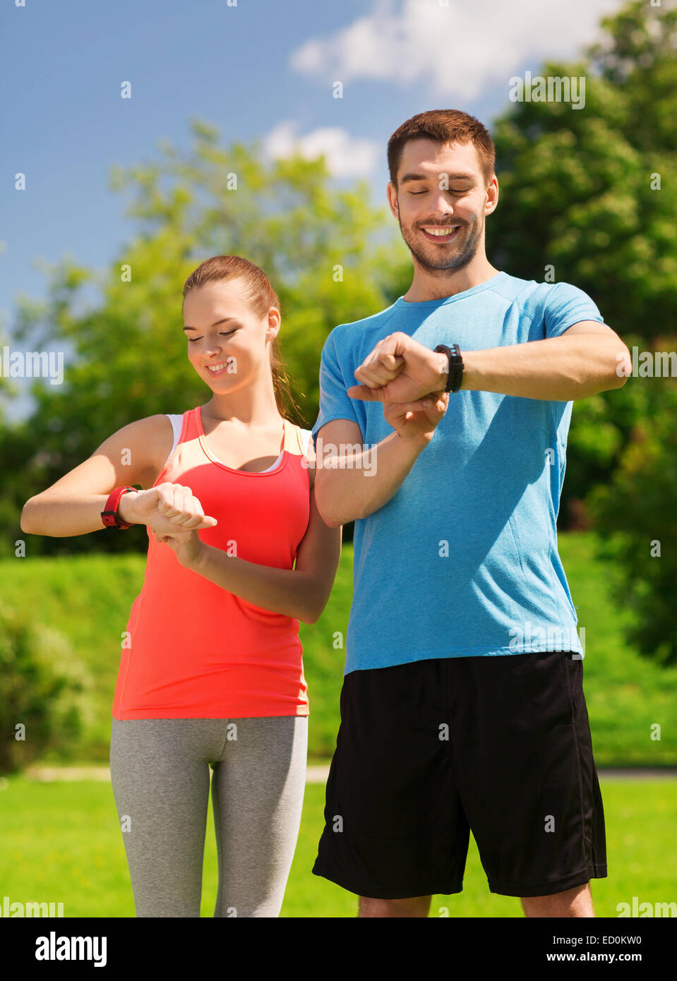 smiling people with heart rate watches outdoors - Stock Image