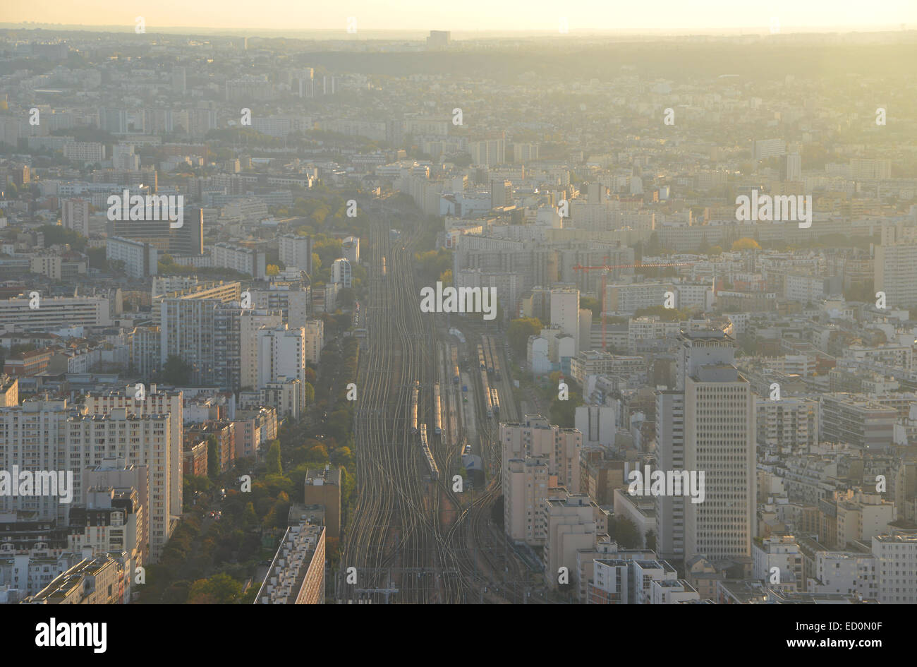 Looking South East along train lines running into Gare Montparnasse as the sun sets over Paris - Stock Image