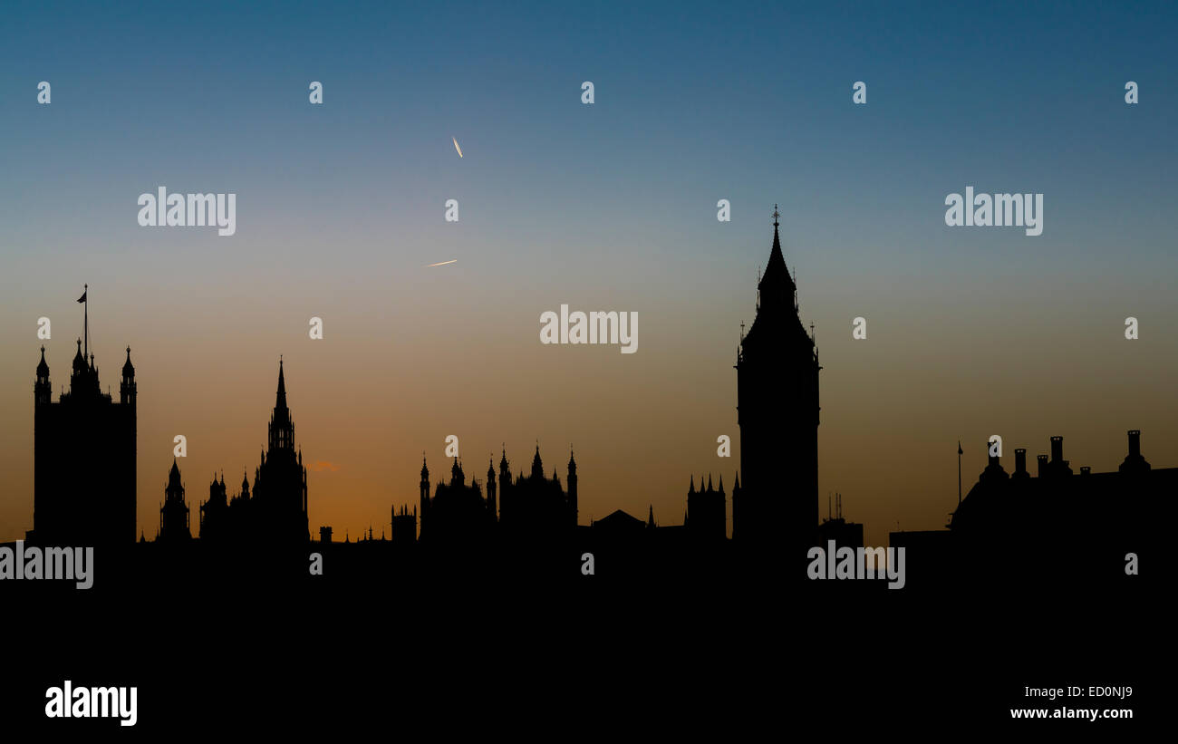 Silhouette of the Houses of Parliament and Big Ben at sunset with contrails of overflying planes in the sky - Stock Image