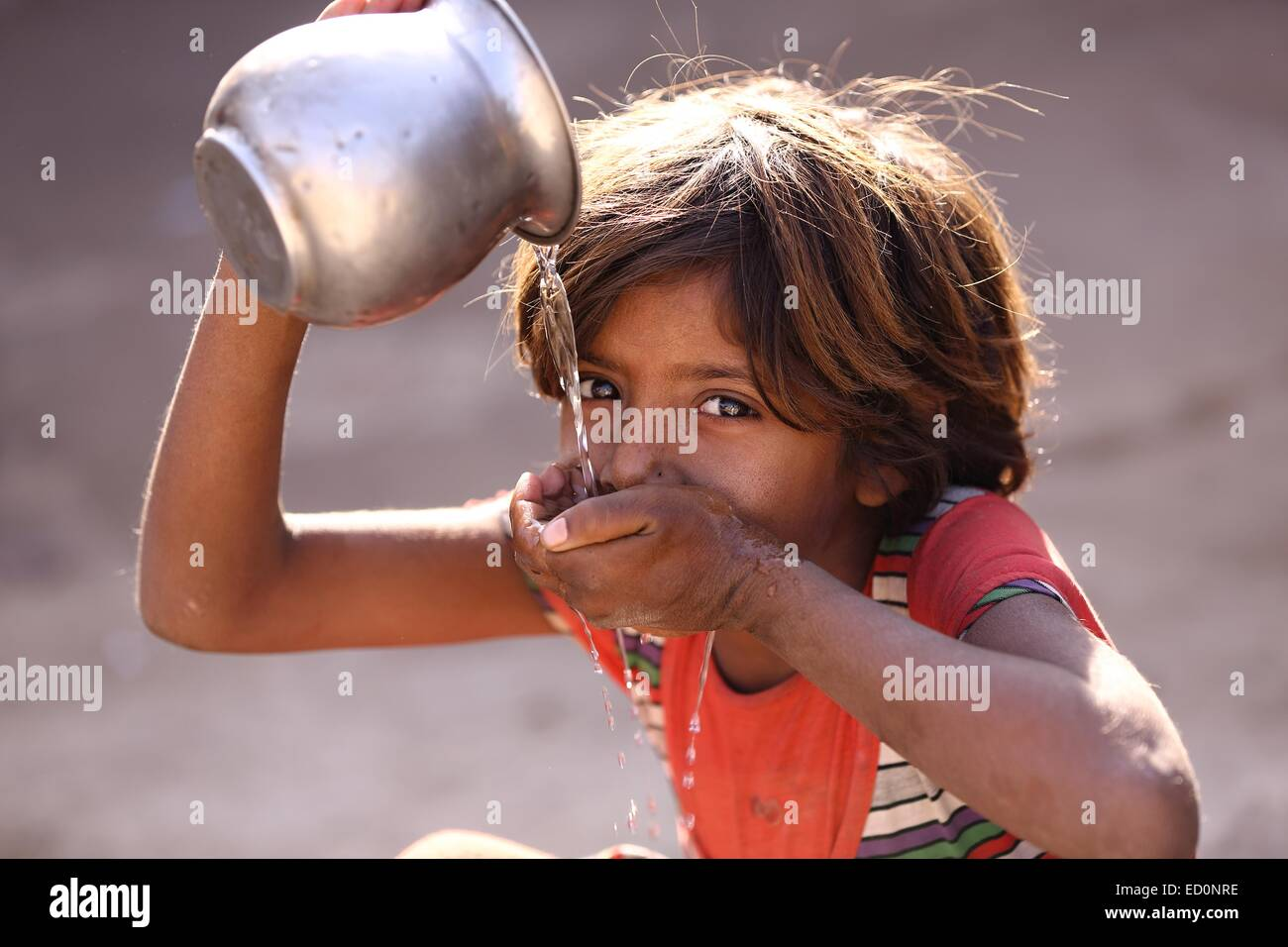 Indian girl drinking water India - Stock Image