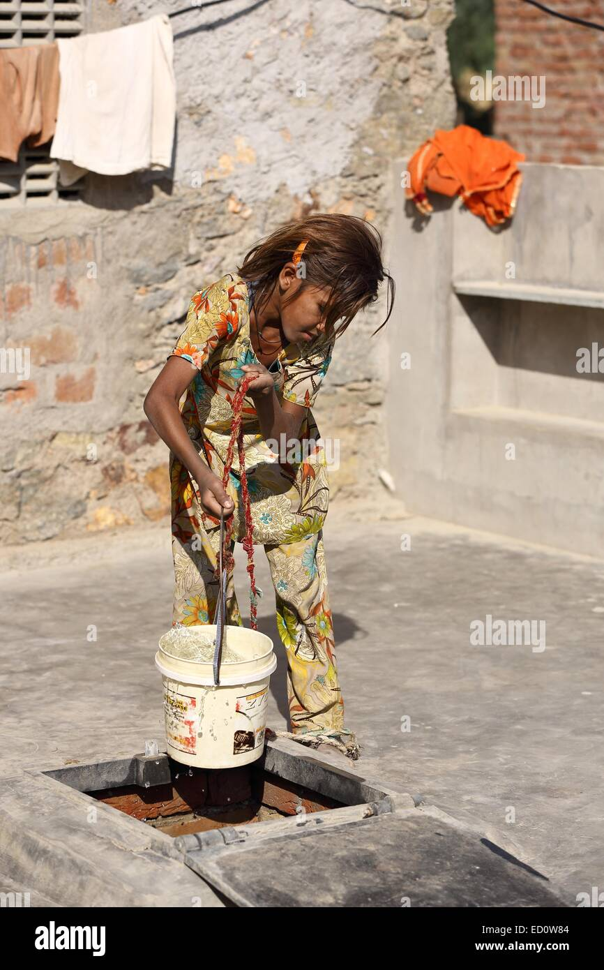 Indian girl carrying a pot of water lifted from a rain water harvesting tank India - Stock Image