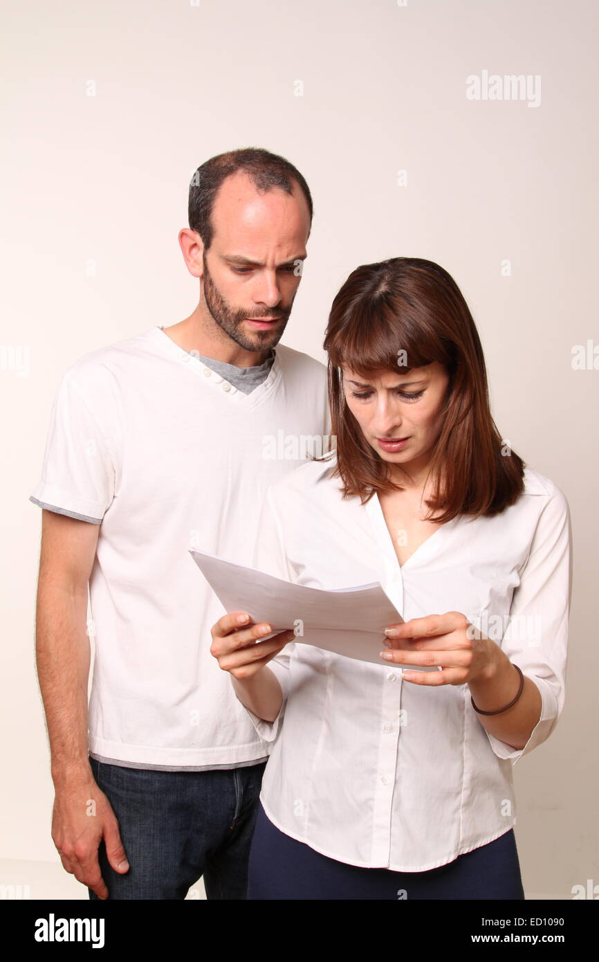 Couple reading letter containing bad news - Stock Image
