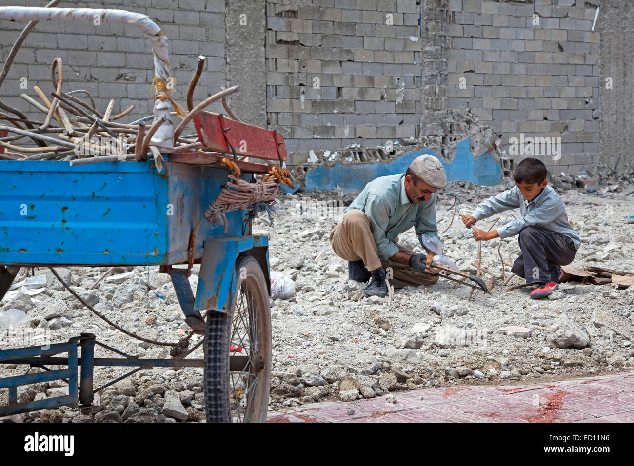 Son helping father recuperating iron with metal saw from debris of collapsed building after earthquake in Van, Eastern - Stock Image