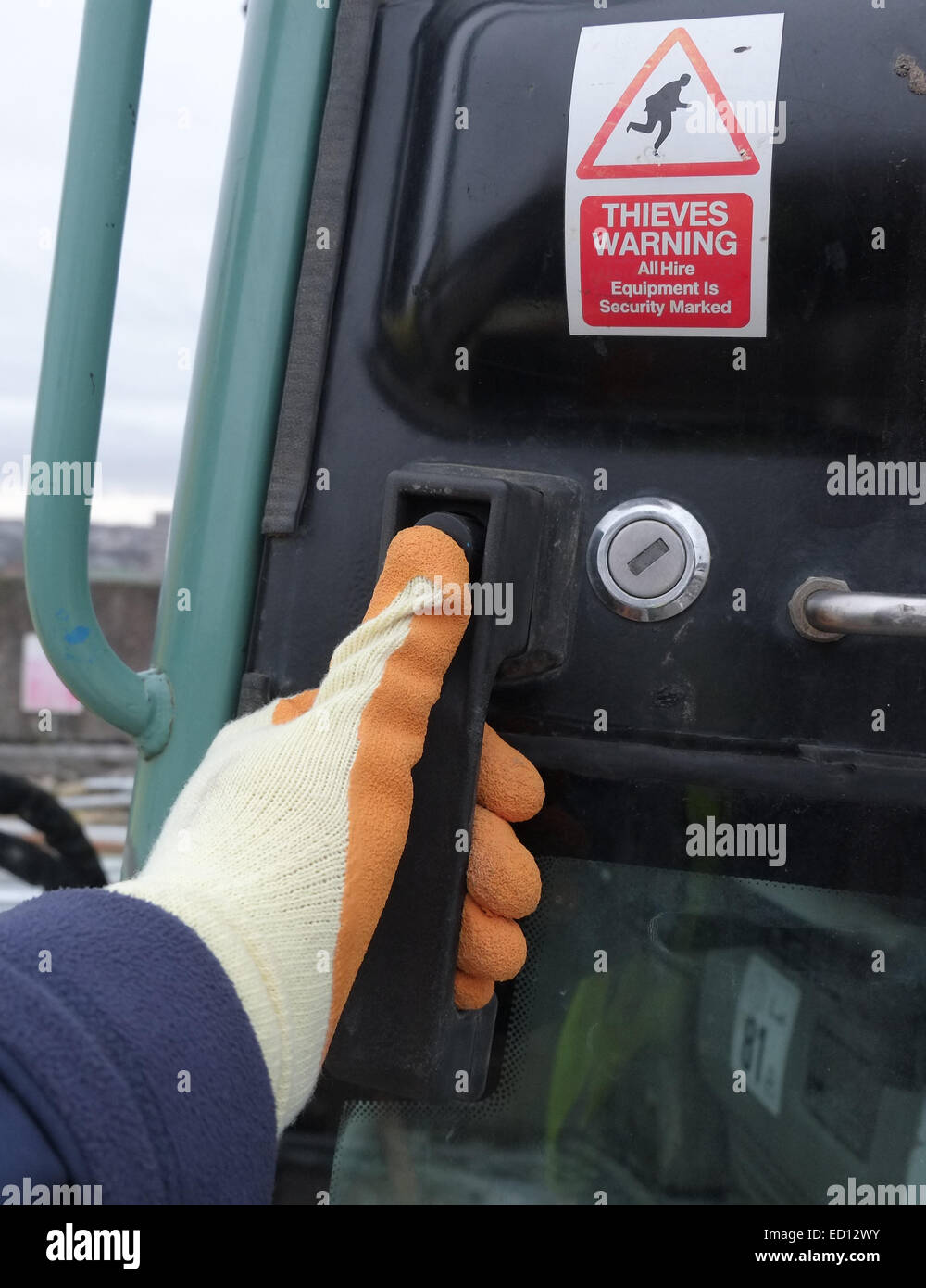 Gloved hand of a construction worker about to open the door of his machine, with theft warning sticker. 22nd December - Stock Image