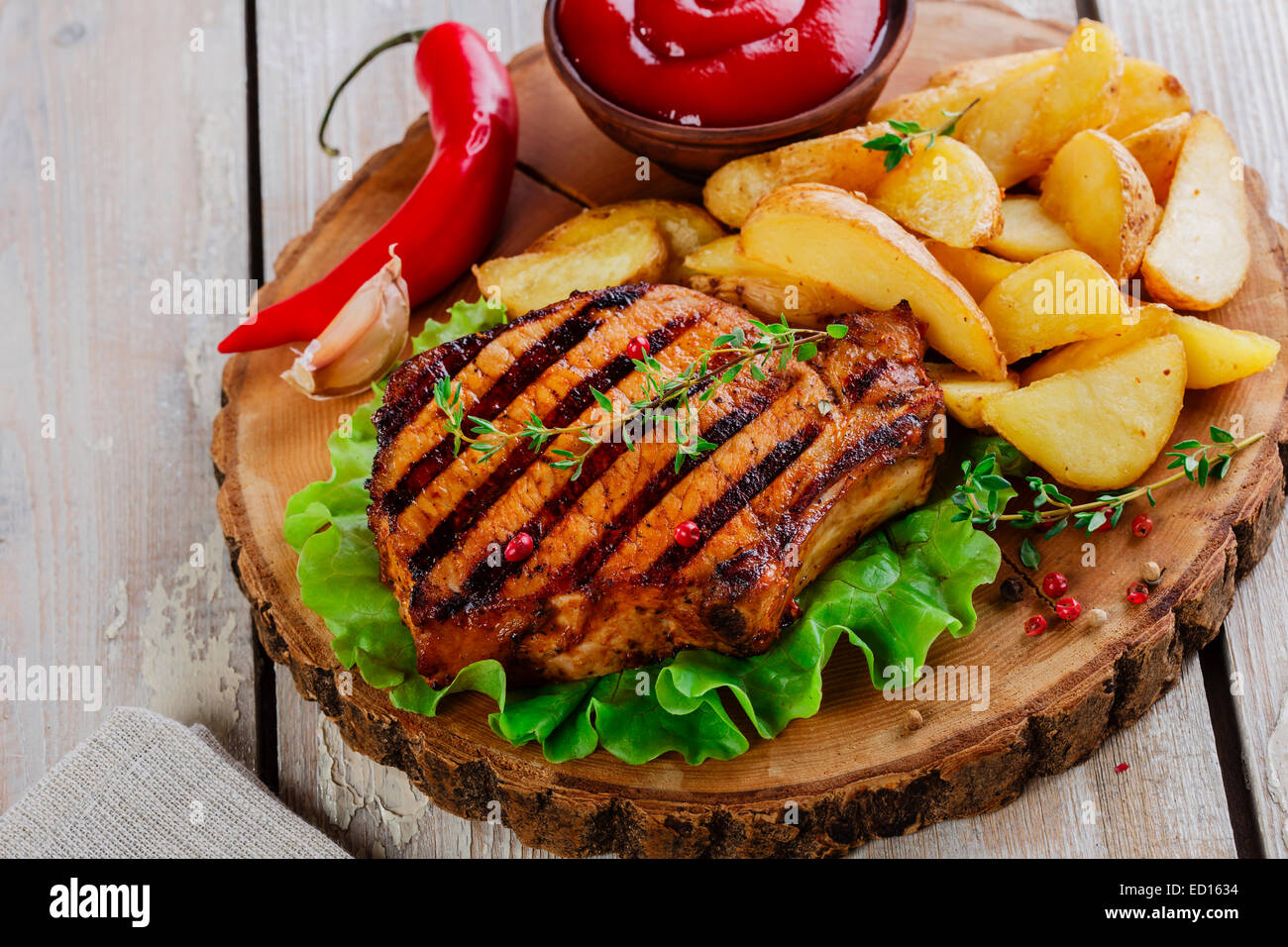 Grilled steak on the bone with potatoes - Stock Image
