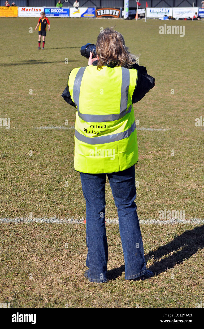 a professional sports photographer taking photographs at a junior rugby game - Stock Image