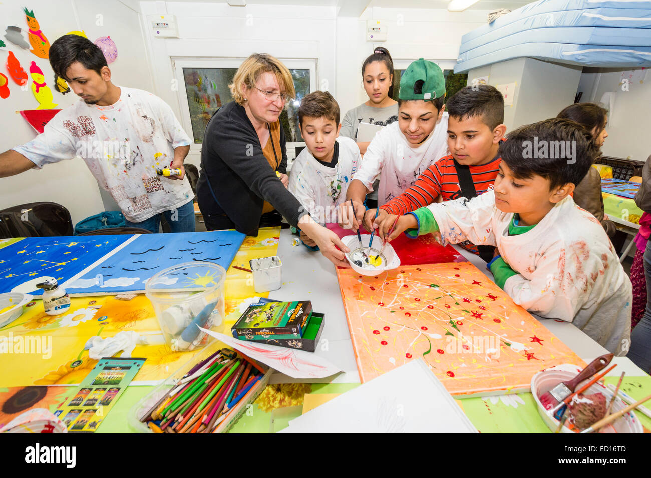 A graphic designer, 2nd from left, works with refugee children in a refugee accomodation. - Stock Image