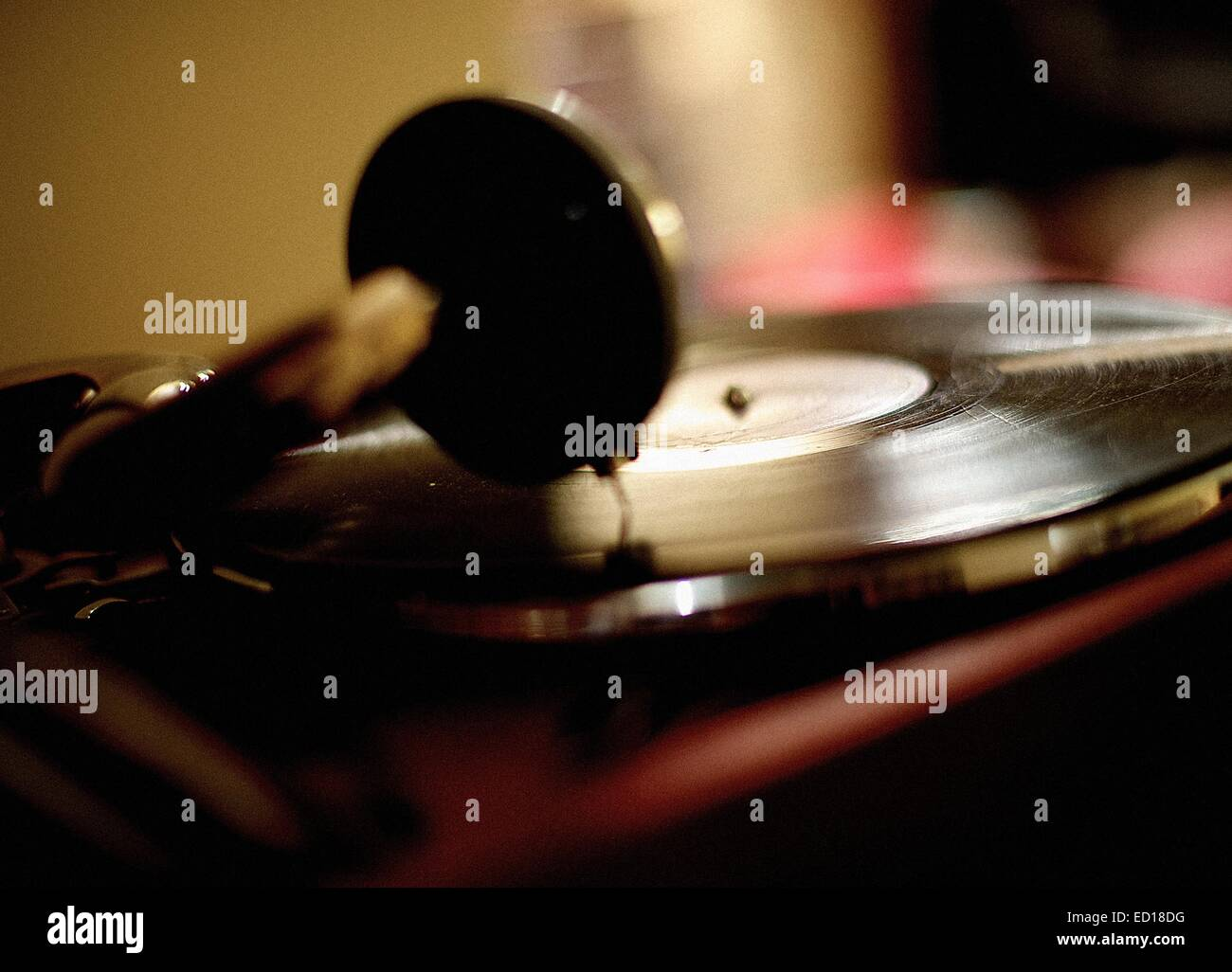 Horizontal shot of the vintage vinyl record player playing scratched LP. - Stock Image
