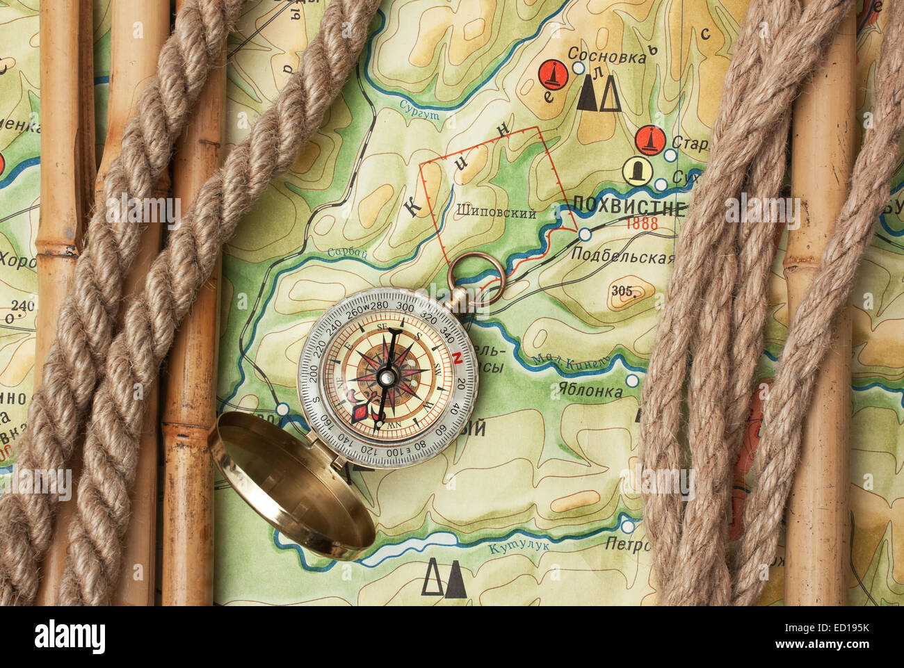 Topographic Map Games.Compass With Ropes And Bamboo On A Topographic Map Stock Photo