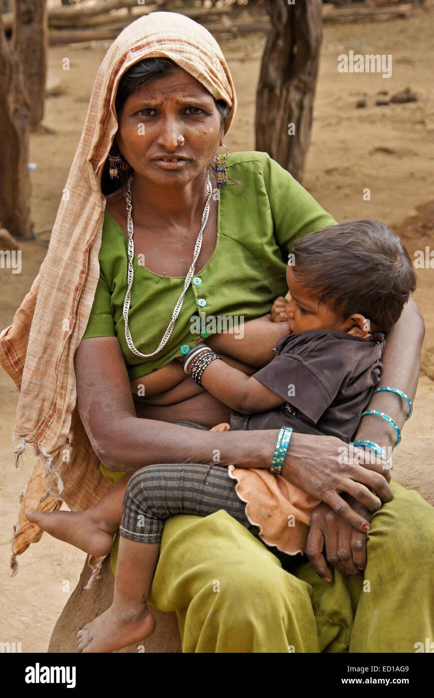 Woman of Adivasi tribe nursing her child in village near Poshina, Gujarat, India - Stock Image
