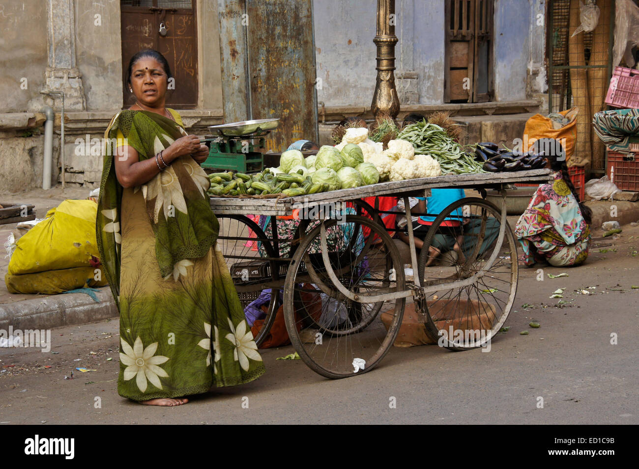 Woman selling produce on street in Old Ahmedabad, Gujarat, India - Stock Image