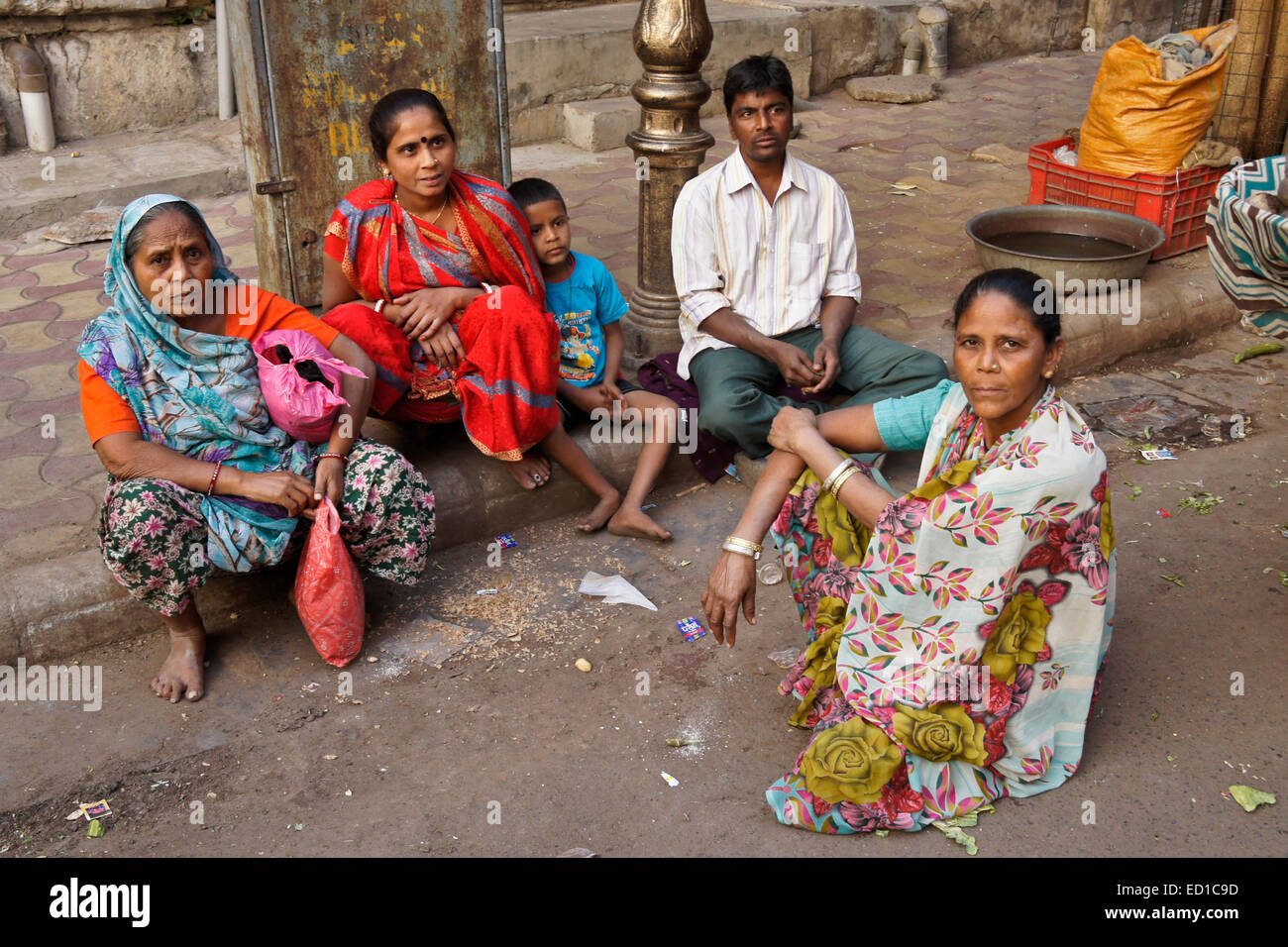 Family sitting on curb in Old Ahmedabad, Gujarat, India - Stock Image