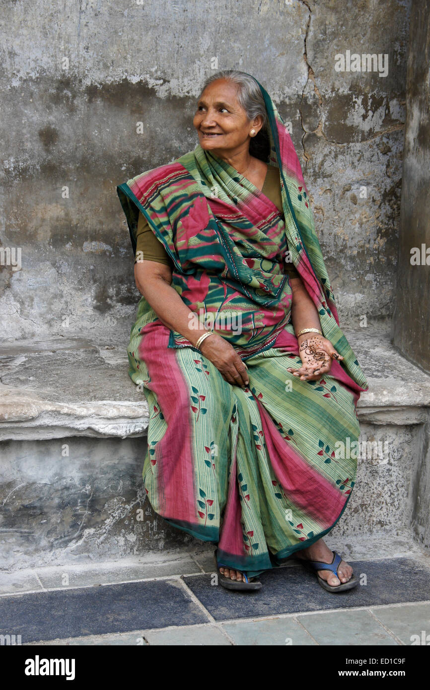 Woman sitting outside home in Old Ahmedabad, Gujarat, India - Stock Image