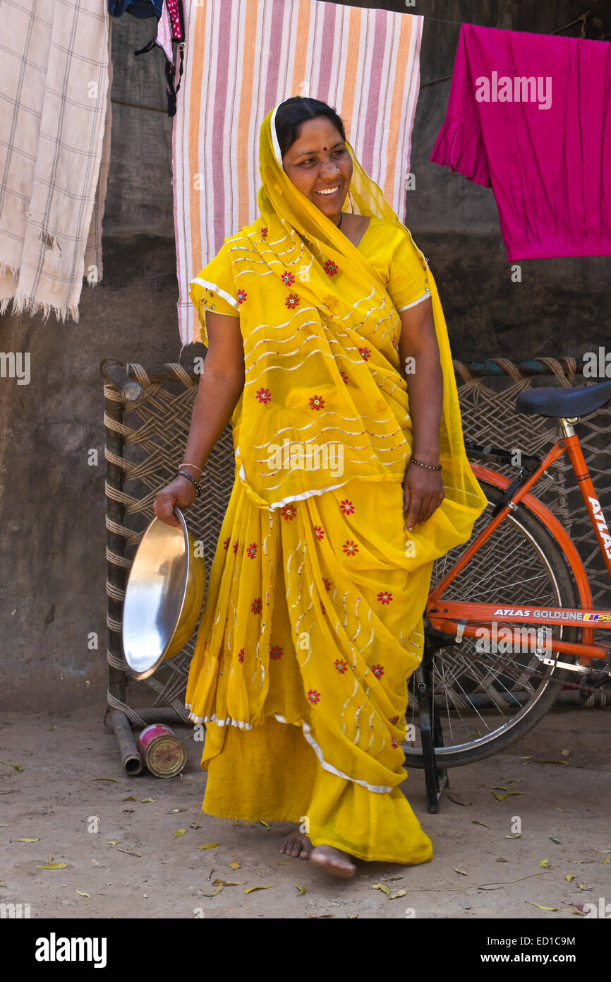 Woman in traditional dress hanging laundry outside her home, Modhera, Gujarat, India - Stock Image
