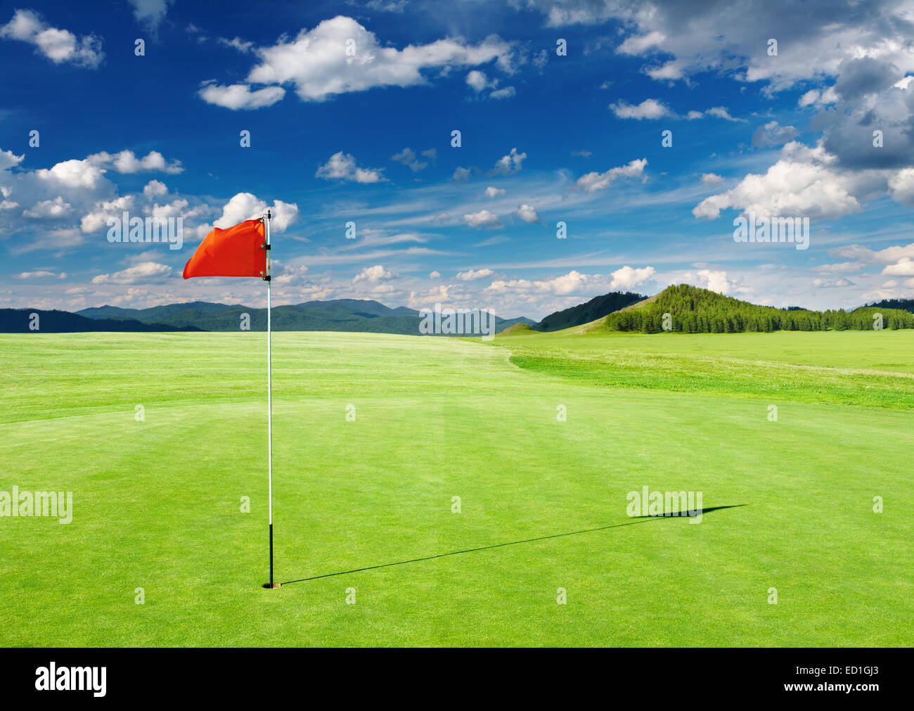 Golf field with red flag in the hole - Stock Image