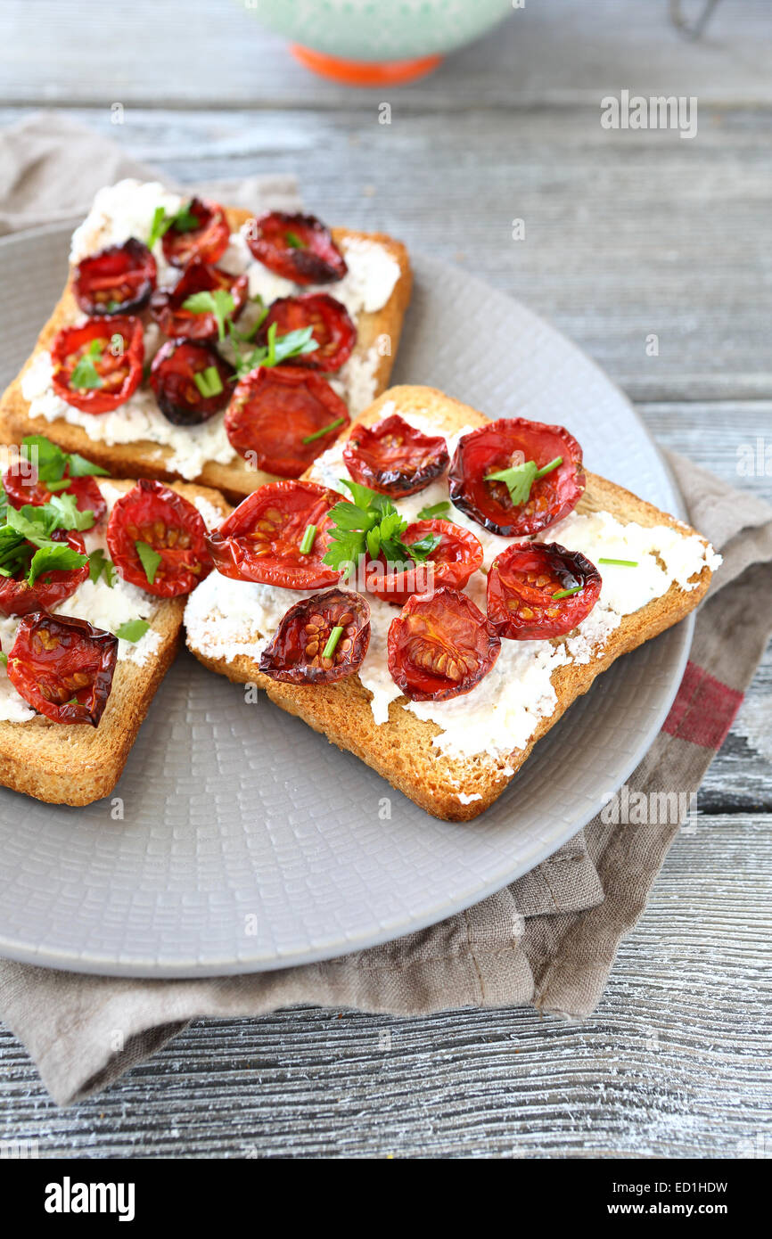 Bruschetta with sun-dried tomatoes and cheese on a plate, food - Stock Image