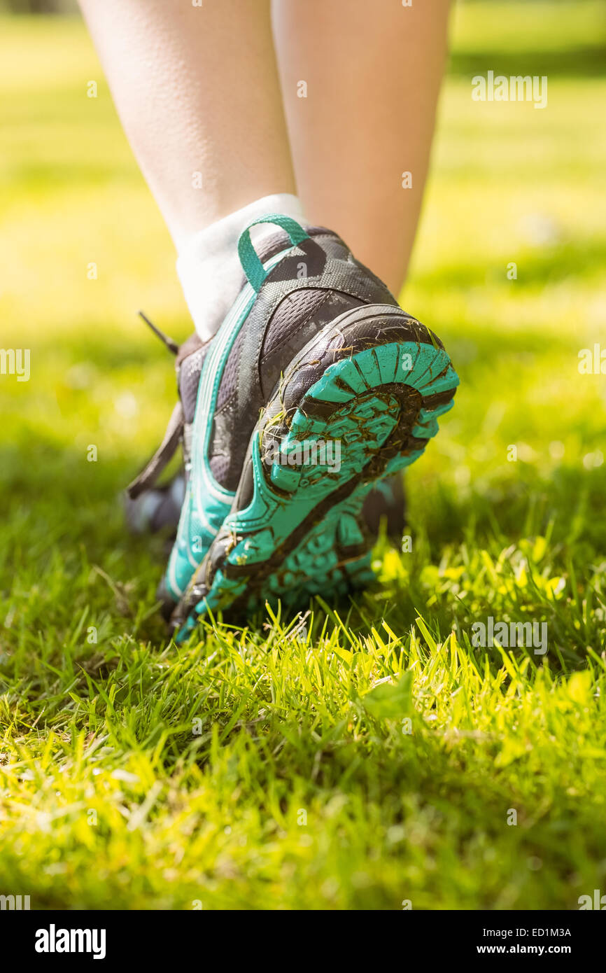 Woman in running shoes stepping on grass - Stock Image
