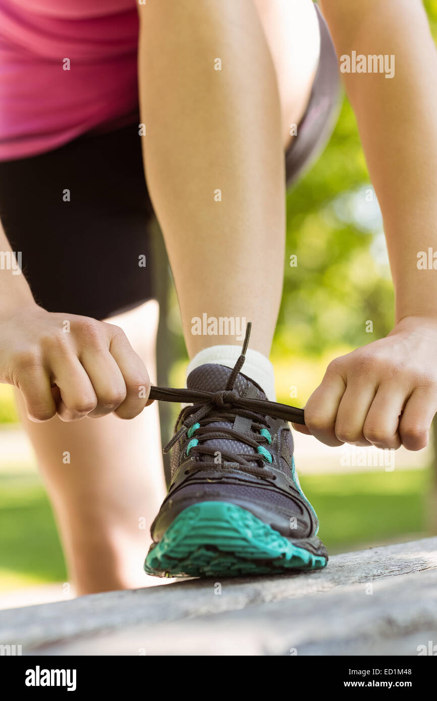 Fit woman tying her shoelace - Stock Image