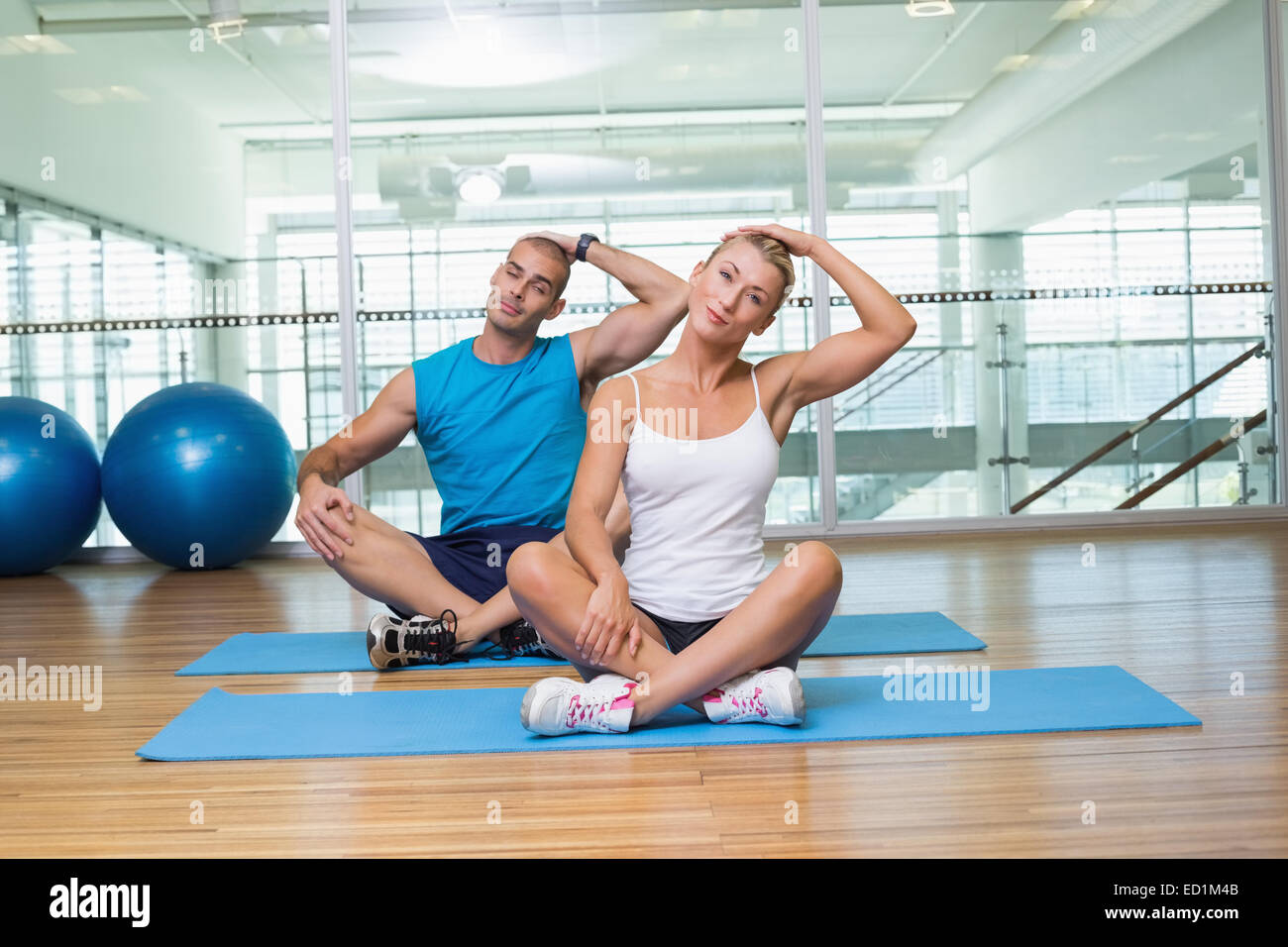 Couple stretching necks in yoga class - Stock Image