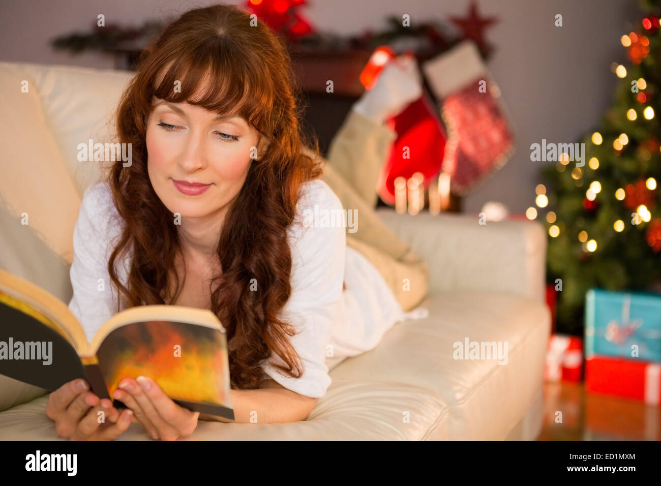 Pretty woman lying on a cosy couch reading book - Stock Image