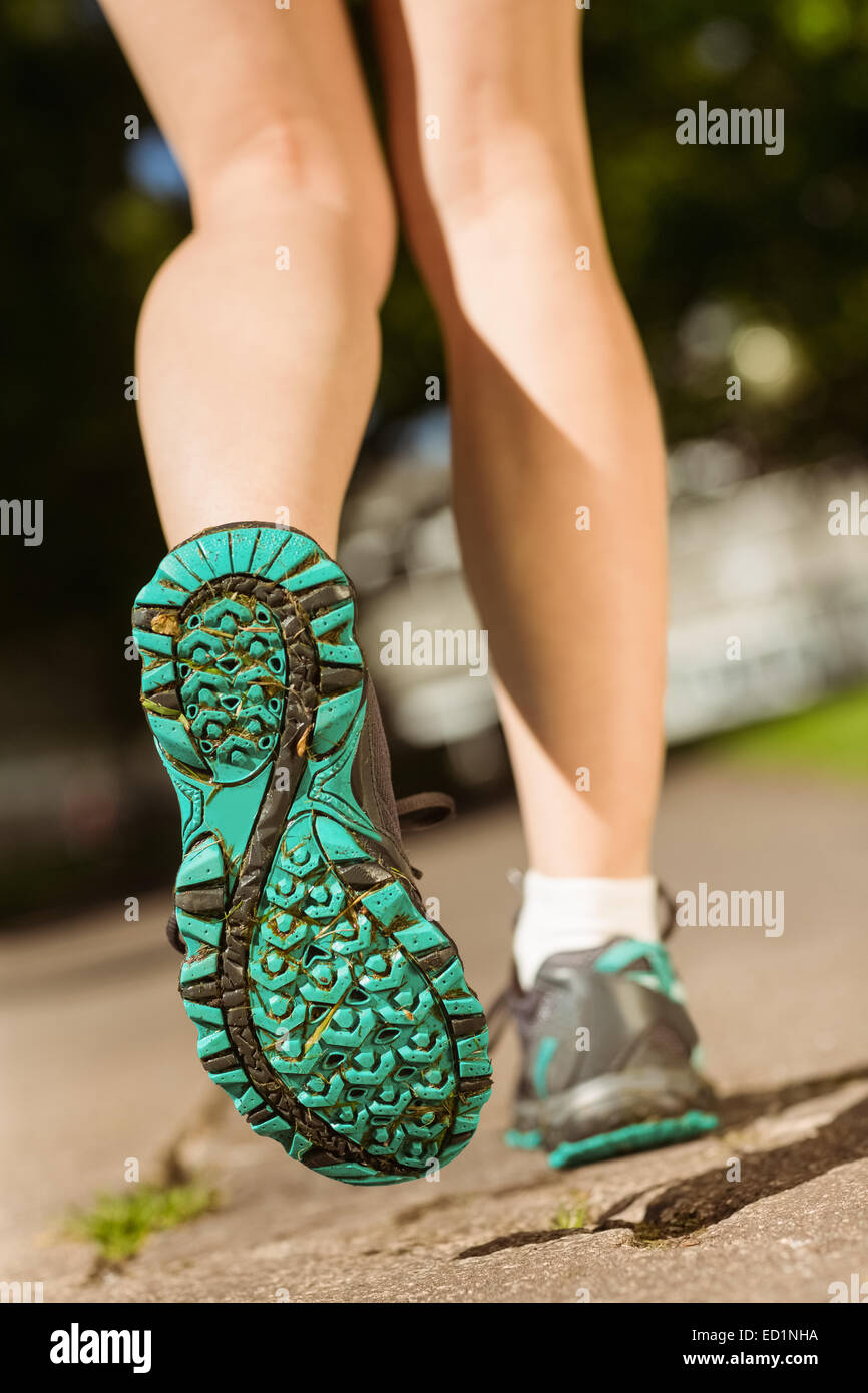 Woman in running shoes stepping on path Stock Photo