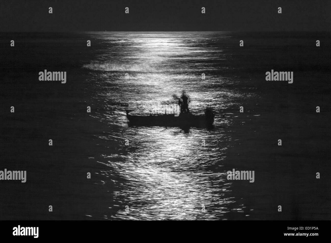 Fishermen Silouette at Full Moon in Torre Archirafi little village in east Sicily - Stock Image