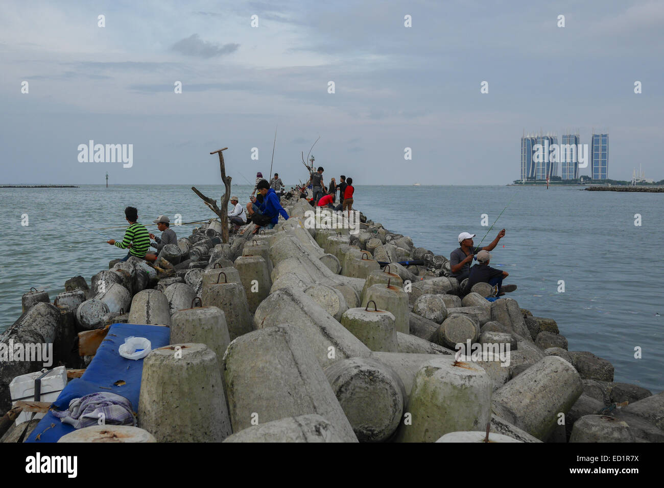 People fishing on tetrapod structures at Muara Angke's groin, North Jakarta. - Stock Image