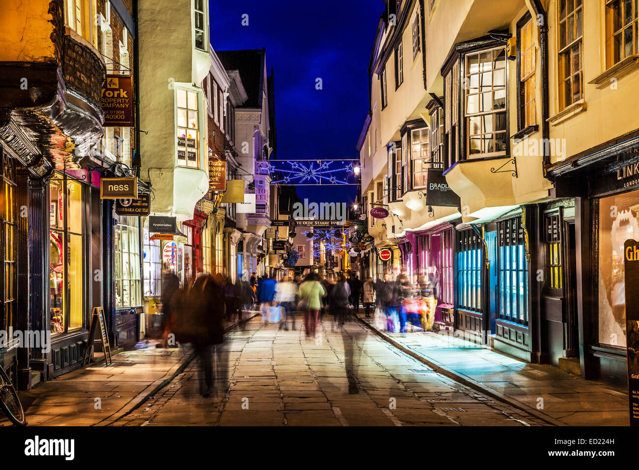 Christmas shoppers hurrying along the historic street of Stonegate in York at twilight. - Stock Image