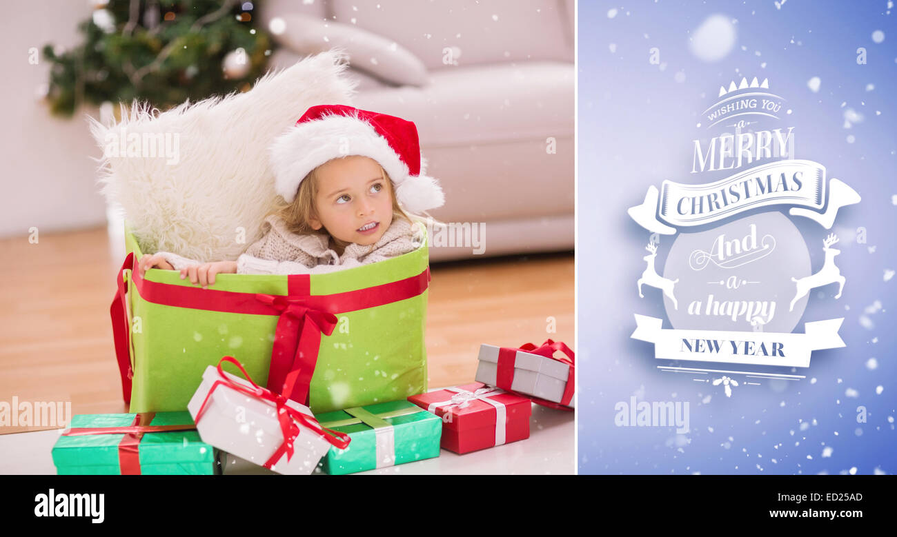 Composite image of cute little girl sitting in giant christmas gift ...