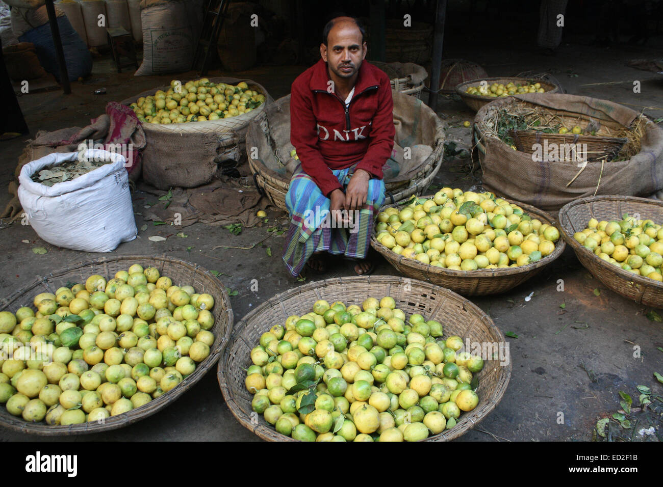 A Bangladeshi lemon's vendor he waits for customers at a wholesale market at karwan Bazar in Dhaka on December - Stock Image