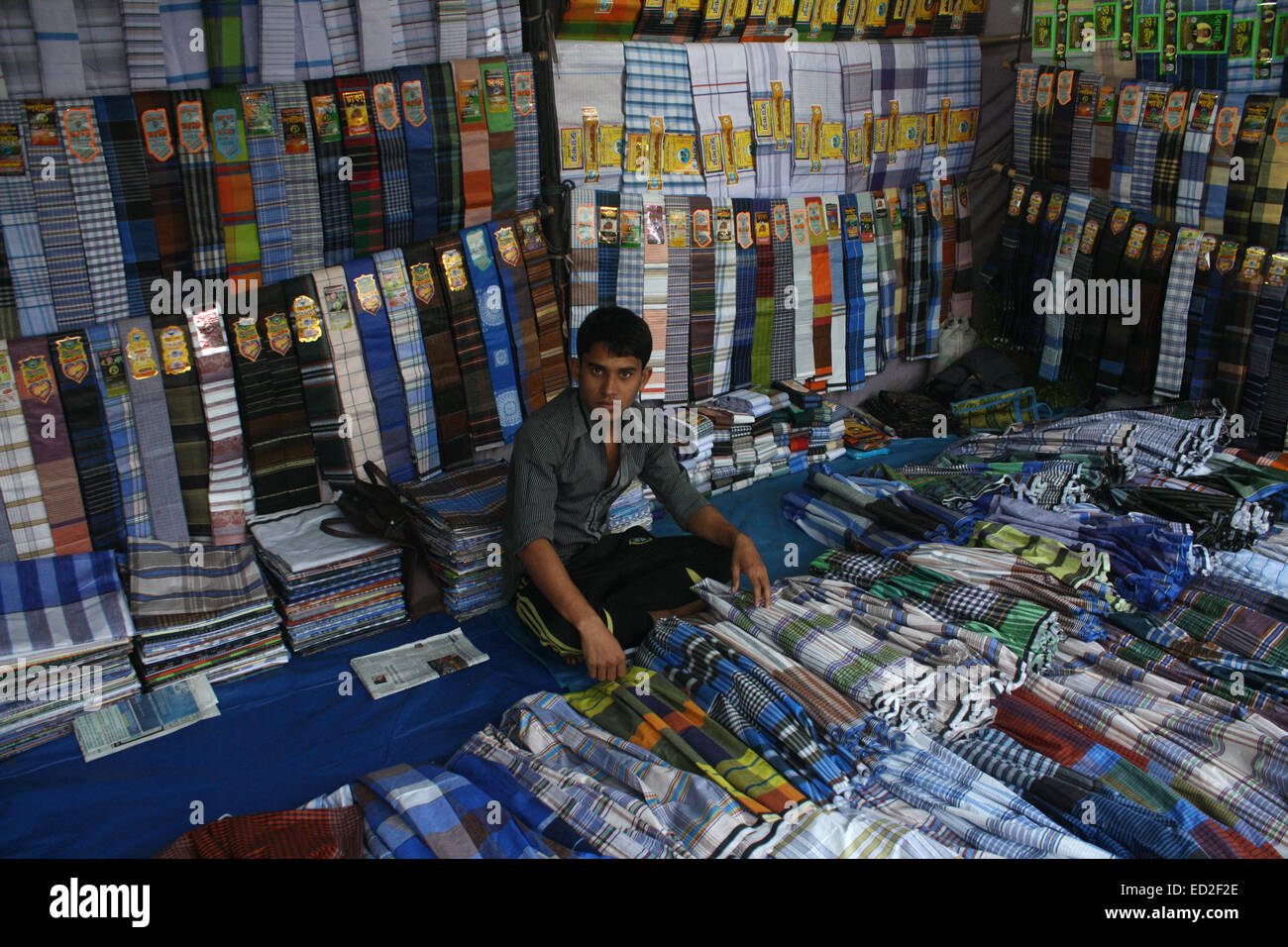 A Bangladeshi clothe vendor he waits for customers at a wholesale market at karwan Bazar in Dhaka on December 24, - Stock Image