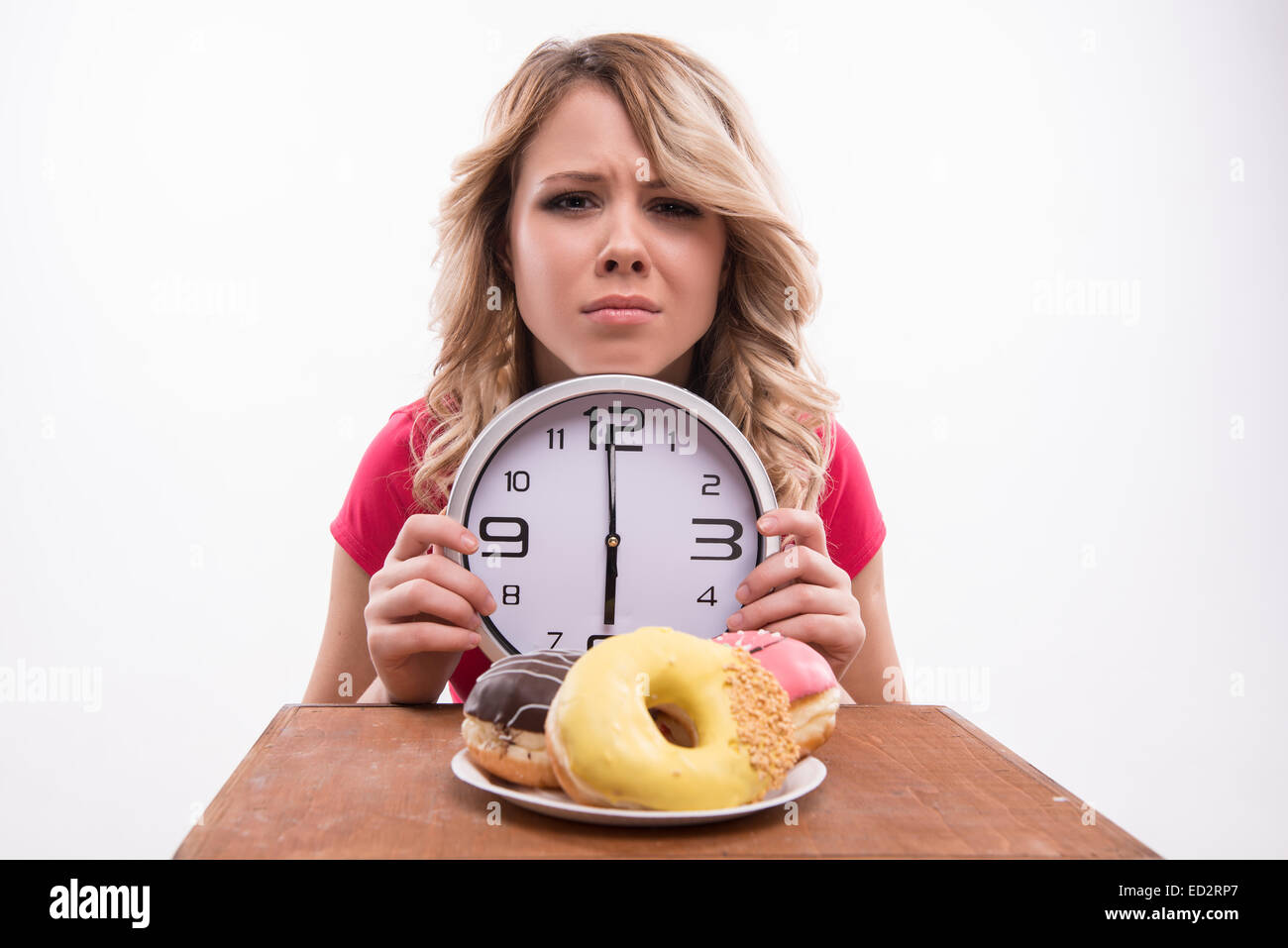 Time for diet slimming. Beautiful woman with clock keeps herself - Stock Image
