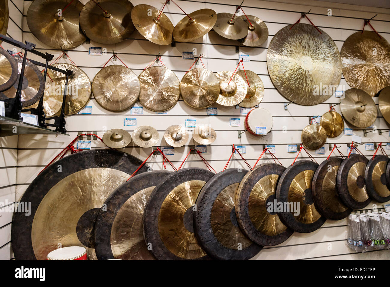 Percussion musical instruments, cymbals and gongs on display at a store in Shanghai, China - Stock Image