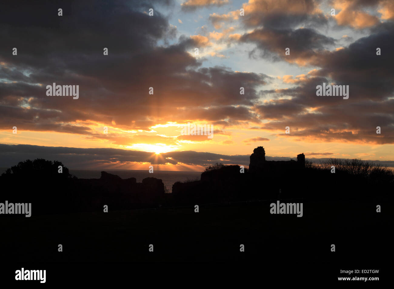 UK Weather Hastings, East Sussex, UK. 24th December 2014. The rays of the setting sun over Hastings Castle on Christmas Stock Photo